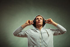 Handsome man with headphones listening to music. Young handsome man with headphones listening to music looking up grunge background Royalty Free Stock Image