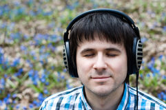 Handsome man in headphones outdoor. Spring Stock Image