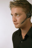 Handsome Man with Headset. Young businessman wearing a headset on grey Stock Photography