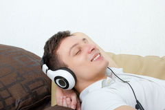 Handsome man with headset listening to music smiling Stock Photography