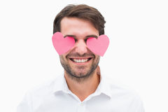 Handsome man with hearts over his eyes. On white background Royalty Free Stock Photo