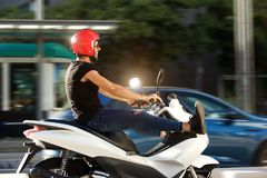 Handsome man with helmet on motorcycle ride in city Royalty Free Stock Photography