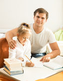 Handsome man helping daughter with homework Royalty Free Stock Photos