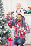 Handsome man helps child to decorate New Year tree. Cheerful father and son are decorating Christmas tree. They are looking at the camera and smiling. The parent stock images