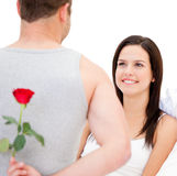 Handsome man hidding a rose from his girlfriend Royalty Free Stock Image