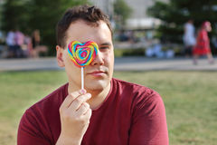 Handsome man hides his eye behind lollipop outdoor Stock Images