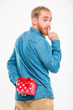 Handsome  man hiding gift behind back and gesturing silence Stock Photos