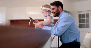 Handsome man with his baby holding tablet stock video