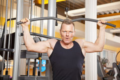 Handsome man in his forties exercising in gym. A handsome man in his forties exercising in a fitness studio training his latissimus and looking into camera Stock Photo