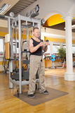 Handsome man in his forties exercising in gym. A handsome man in his forties exercising in a fitness studio and training his biceps Royalty Free Stock Images