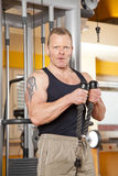 Handsome man in his forties exercising in gym. A handsome man in his forties exercising in a fitness studio training his biceps and looking into camera Stock Photo