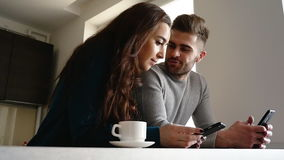 Handsome man and his girlfriend using phones in the kitchen. Handsome man and his girlfriend using phones in the kitchen stock video