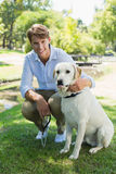 Handsome man with his labrador in the park smiling at camera Royalty Free Stock Images