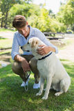 Handsome man with his labrador in the park Stock Photography