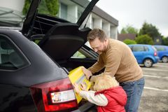 Handsome man and his little son going to vacations, loading their suitcase in car trunk. Automobile trip in the countryside. stock image