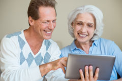 Handsome man with his mom. Modern. Happy senior mom and son using tablet pc computer Stock Photos