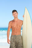 Handsome man with his surfboard Royalty Free Stock Photography