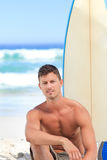Handsome man with his surfboard. And looking the camera Stock Image