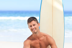 Handsome man with his surfboard Stock Photography