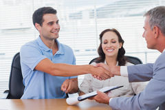 Handsome man with his wife shaking hands with estate agent Stock Photos