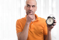 Handsome man holding an alarm clock Royalty Free Stock Image
