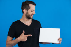 Handsome man holding a blank placard. Against blue background Royalty Free Stock Photo