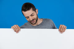 Handsome man holding a blank placard. Against blue background Stock Photos