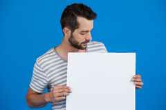 Handsome man holding a blank placard. Against blue background Stock Images