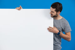 Handsome man holding a blank placard. Against blue background Stock Photo