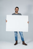Handsome man holding a blank placard. Against grey background Stock Image