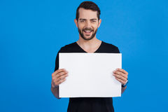 Handsome man holding a blank placard. Portrait of a handsome man holding a blank placard against blue background Royalty Free Stock Photo