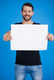Handsome man holding a blank placard. Portrait of a handsome man holding a blank placard against blue background Royalty Free Stock Photography
