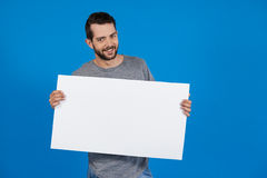 Handsome man holding a blank placard. Portrait of a handsome man holding a blank placard against blue background Stock Image