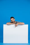 Handsome man holding a blank placard. Portrait of a handsome man holding a blank placard against blue background Stock Photos