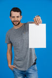 Handsome man holding a blank placard. Portrait of a handsome man holding a blank placard against blue background Stock Photography