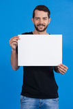 Handsome man holding a blank placard. Portrait of a handsome man holding a blank placard against blue background Stock Images