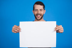 Handsome man holding a blank placard. Portrait of a handsome man holding a blank placard against blue background Stock Photo