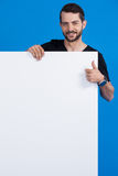Handsome man holding a blank placard Royalty Free Stock Images