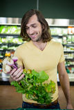 Handsome man holding bunch of fresh turnips in organic section Royalty Free Stock Images