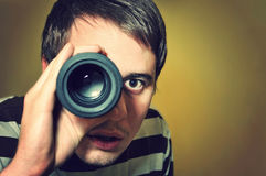 Handsome man holding camera lens like spyglass. Handsome young man holding camera lens like it was spyglass Royalty Free Stock Image