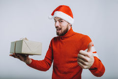 Handsome man holding a christmas gift. Isolated on white background. Handsome man holding a christmas gift in one hand and showing that everything is ok or cool Stock Photos