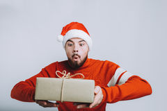 Handsome man holding a christmas gift. Isolated on white background. Handsome man in red sweater and Santa`s hat holding a christmas gift. Young guy is wondering Stock Photo