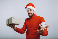 Handsome man holding a christmas gift. Isolated on white background. Handsome man in red winter sweater holding a christmas gift. H is wearing Santa Claus hat Stock Photography