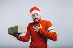 Handsome man holding a christmas gift. Isolated on white background. Handsome man in Santa`s hat holding a christmas gift. Happy guy put his hand on chest asking Royalty Free Stock Image