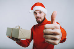 Handsome man holding a christmas gift. Isolated on white background. Handsome man in warm red sweater holding a christmas gift. Smiling guy in Santa`s hat is Royalty Free Stock Photos