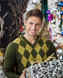 Handsome Man Holding Christmas Gift In Store Royalty Free Stock Images