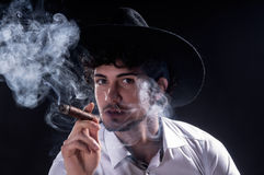 Handsome man holding cigar with smoke Stock Photo