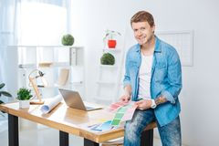 Handsome man holding color palettes and smiling. Color palettes. Cheerful handsome positive designer sitting on the table and smiling while holding bright color royalty free stock photography