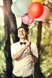 Handsome man holding colorful ballons. Handsome young man holding in his hands colorful ballons and smiling Royalty Free Stock Image