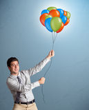 Handsome man holding colorful balloons Stock Photos